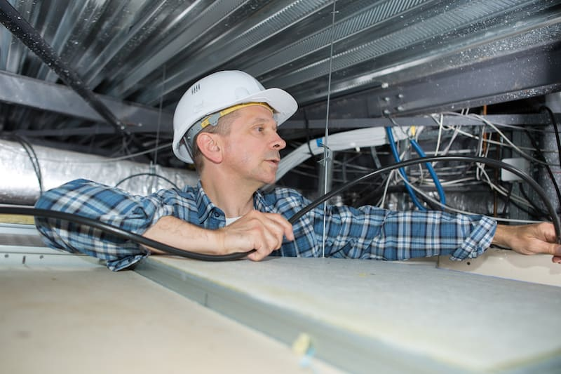 electrician in attic doing electrical home inspection