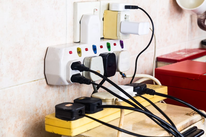 Multiple electricity plugs on adapter risk overloading and dangerous
