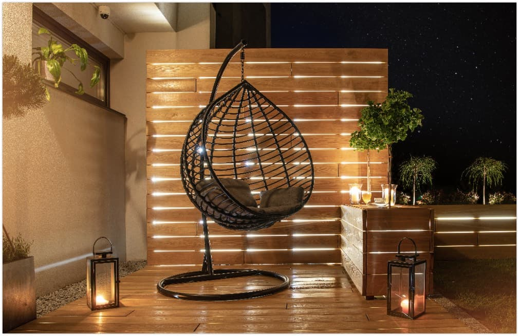 Starry Night Time in Stylish Backyard Garden with Wooden Porch with Wall and Planters Illuminated by Modern LED Lighting